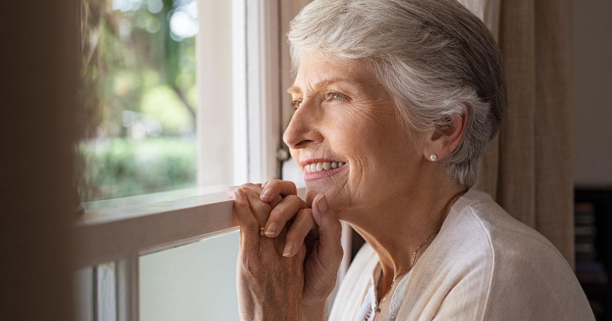 femme séniors souriante regardant par la fenêtre
