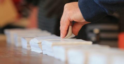 main prenant un bulletin d'élection